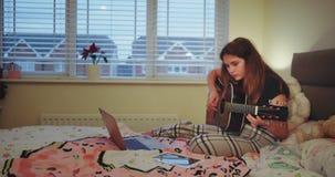 Muchacha feliz del adolescente que juega en una guitarra en su sitio y usar auriculares muy concentrados en el extremo que ella m almacen de video