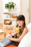 Muchacha feliz del adolescente que se sienta a casa en el sofá Foto de archivo libre de regalías