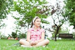 Muchacha feliz del adolescente que se sienta en la hierba Fotos de archivo libres de regalías