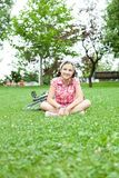Muchacha feliz del adolescente que se sienta en la hierba Foto de archivo libre de regalías