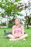 Muchacha feliz del adolescente que se sienta en la hierba Imagen de archivo libre de regalías