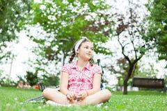 Muchacha feliz del adolescente que se sienta en la hierba Fotografía de archivo
