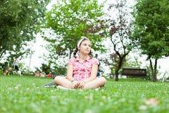 Muchacha feliz del adolescente que se sienta en la hierba Fotos de archivo