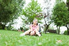 Muchacha feliz del adolescente que se sienta en la hierba Foto de archivo