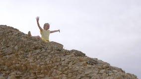 Muchacha feliz del adolescente que se sienta en las escaleras rocosas y la mano que agita para los saludos almacen de metraje de vídeo