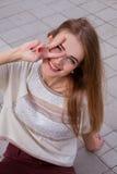 Muchacha feliz del adolescente que sonríe y que muestra la muestra de la victoria Fotos de archivo