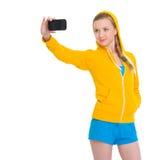 Muchacha feliz del adolescente que toma la foto con el teléfono celular Foto de archivo