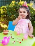 Muchacha feliz del bebé, comiendo gummies riendo y sonriendo en fiesta del té al aire libre imagen de archivo