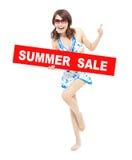 Muchacha feliz del bikini que lleva a cabo una muestra de la venta del verano Fotografía de archivo