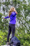 Muchacha feliz del caminante que celebra en el top de la montaña con los brazos para arriba Imagen de archivo libre de regalías