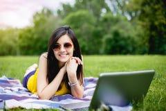 Muchacha feliz del estudiante del adolescente que usa un ordenador portátil en un campus o un parque que miente en la hierba Imágenes de archivo libres de regalías