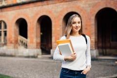 Muchacha feliz del estudiante con el bolso y los cuadernos de escuela al aire libre Fotografía de archivo libre de regalías