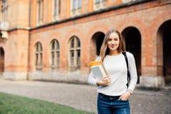 Muchacha feliz del estudiante con el bolso y los cuadernos de escuela al aire libre Imágenes de archivo libres de regalías
