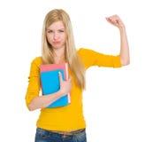 Muchacha feliz del estudiante con el libro que muestra el bíceps Imágenes de archivo libres de regalías