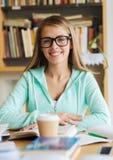Muchacha feliz del estudiante con el libro y el café en biblioteca Fotos de archivo libres de regalías