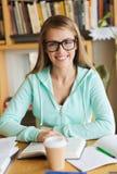 Muchacha feliz del estudiante con el libro y el café en biblioteca Foto de archivo