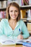 Muchacha feliz del estudiante con el libro y pluma en biblioteca Fotografía de archivo