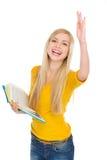 Muchacha feliz del estudiante con la mano de levantamiento del libro a la respuesta Imágenes de archivo libres de regalías