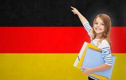 Muchacha feliz del estudiante con las carpetas que señala el finger Fotografía de archivo libre de regalías