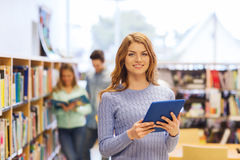 Muchacha feliz del estudiante con PC de la tableta en biblioteca Foto de archivo