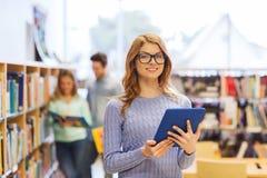 Muchacha feliz del estudiante con PC de la tableta en biblioteca Imágenes de archivo libres de regalías