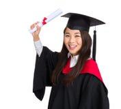 Muchacha feliz del estudiante de tercer ciclo en un vestido académico con el diploma Fotos de archivo libres de regalías