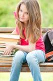 Muchacha feliz del estudiante en banco con la pila de libros Fotografía de archivo libre de regalías