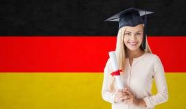 Muchacha feliz del estudiante en casquillo del soltero con el diploma Fotos de archivo libres de regalías