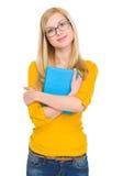 Muchacha feliz del estudiante en los vidrios que abrazan el libro Imagen de archivo libre de regalías
