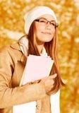 Muchacha feliz del estudiante en parque del otoño Foto de archivo libre de regalías