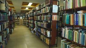 Muchacha feliz del estudiante o mujer joven con el libro que camina en biblioteca almacen de video