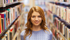 Muchacha feliz del estudiante o mujer joven en biblioteca Foto de archivo