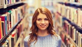 Muchacha feliz del estudiante o mujer joven en biblioteca Fotos de archivo
