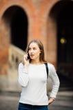 Muchacha feliz del estudiante que camina y que invita al teléfono móvil al aire libre con Uni un fondo Foto de archivo libre de regalías
