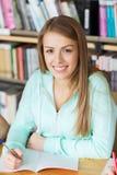 Muchacha feliz del estudiante que escribe al cuaderno en biblioteca Fotografía de archivo libre de regalías