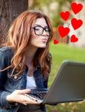 Muchacha feliz del estudiante que escribe al cuaderno en el campus fotos de archivo