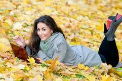 Muchacha feliz del estudiante que miente en hojas de otoño Fotos de archivo