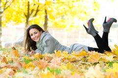 Muchacha feliz del estudiante que miente en otoño Imágenes de archivo libres de regalías