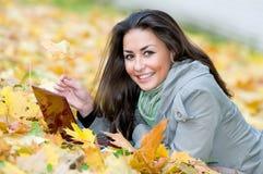 Muchacha feliz del estudiante que miente en otoño Fotos de archivo libres de regalías