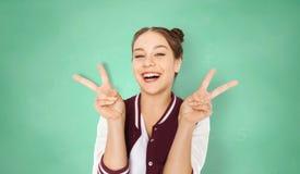 Muchacha feliz del estudiante que muestra el signo de la paz sobre verde Fotografía de archivo libre de regalías