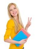 Muchacha feliz del estudiante que muestra gesto de la victoria Fotos de archivo libres de regalías