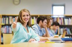 Muchacha feliz del estudiante que muestra los pulgares para arriba en biblioteca Imágenes de archivo libres de regalías