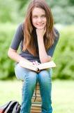 Muchacha feliz del estudiante que se sienta en la pila de libros Fotografía de archivo libre de regalías