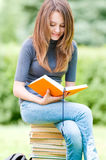 Muchacha feliz del estudiante que se sienta en la pila de libros Fotografía de archivo