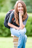 Muchacha feliz del estudiante que se sienta en los libros Imagen de archivo libre de regalías
