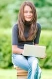 Muchacha feliz del estudiante que trabaja en el ordenador portátil Fotografía de archivo libre de regalías