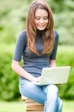 Muchacha feliz del estudiante que trabaja en el ordenador portátil Fotos de archivo libres de regalías