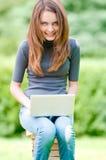 Muchacha feliz del estudiante que trabaja en el ordenador portátil Imagen de archivo