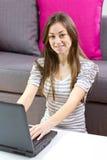 Muchacha feliz del estudiante que usa la computadora portátil Imagenes de archivo