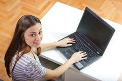Muchacha feliz del estudiante que usa la computadora portátil Imagen de archivo libre de regalías